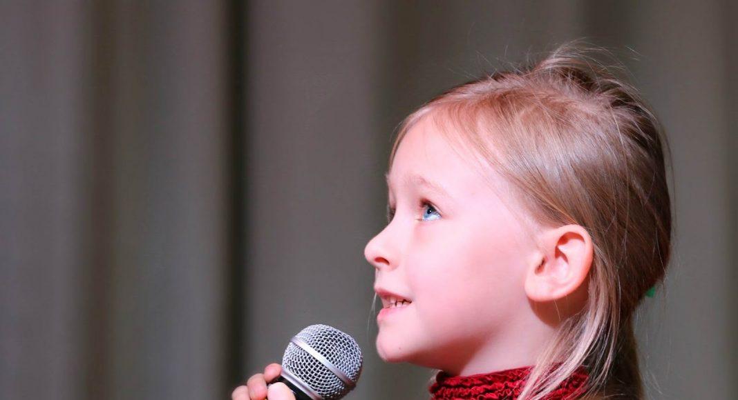 Dziecko ćwiczące śpiew pod okiem nauczyciela