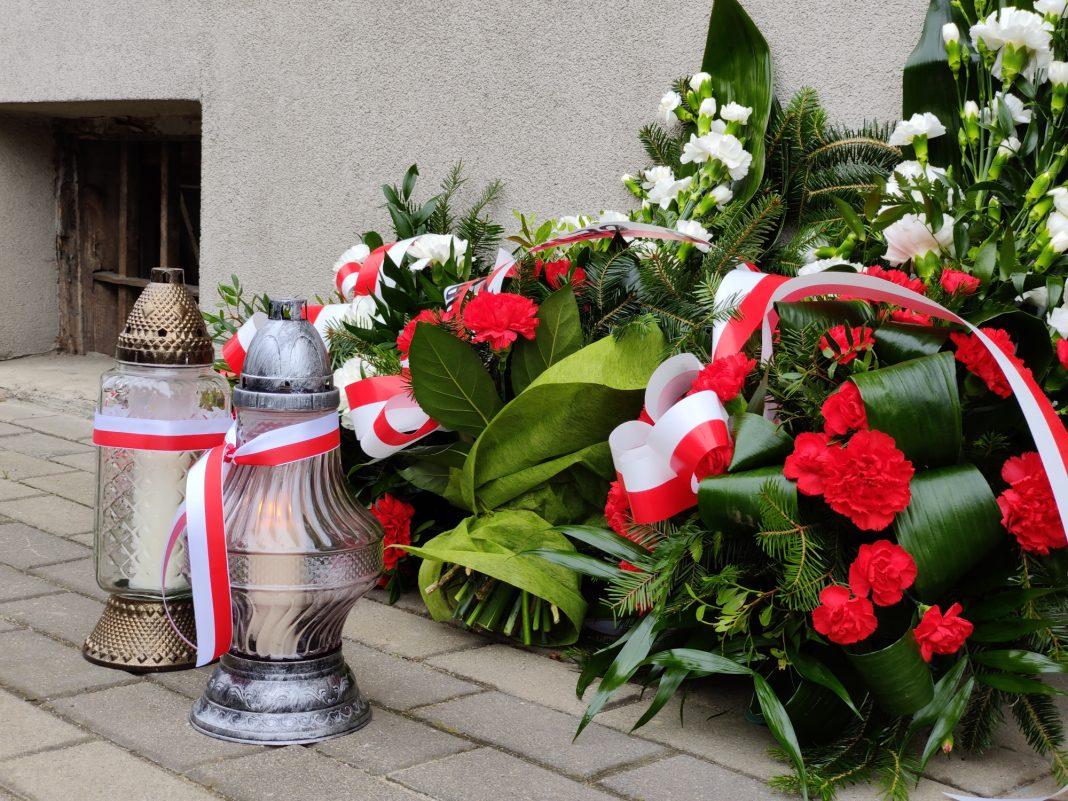 Kwiaty i znicze pod tablicą upamiętniającą ofiary Powiatowego Urzędu Bezpieczeństwa Publicznego w Jaśle