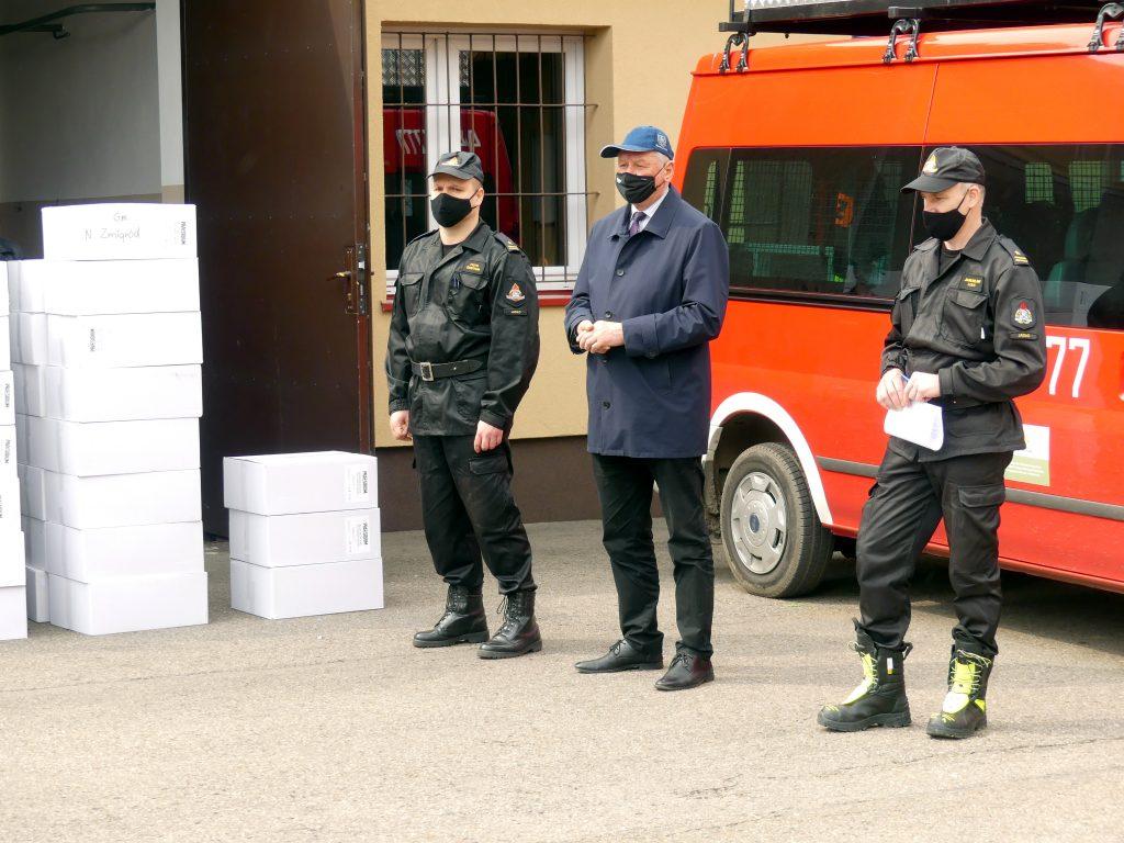 Komendant powiatowy państwowej straży pożarnej w Jaśle, starosta jasielski, zastępca komendanta powiatowego państwowej straży pożarnej w Jaśle, przed garażem pudła z maseczkami chirurgicznymi