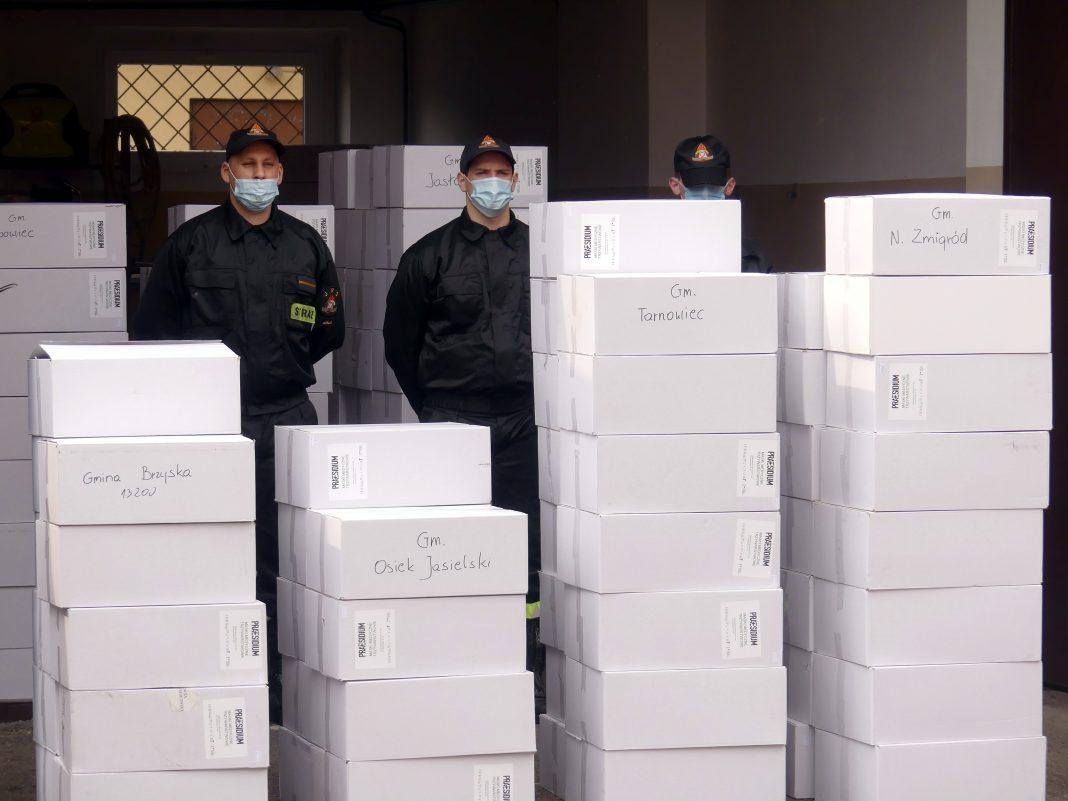Strażacy komendy Powiatowej Państwowej Straży Pożarnej w Jaśle odbierają pudełka z maseczkami