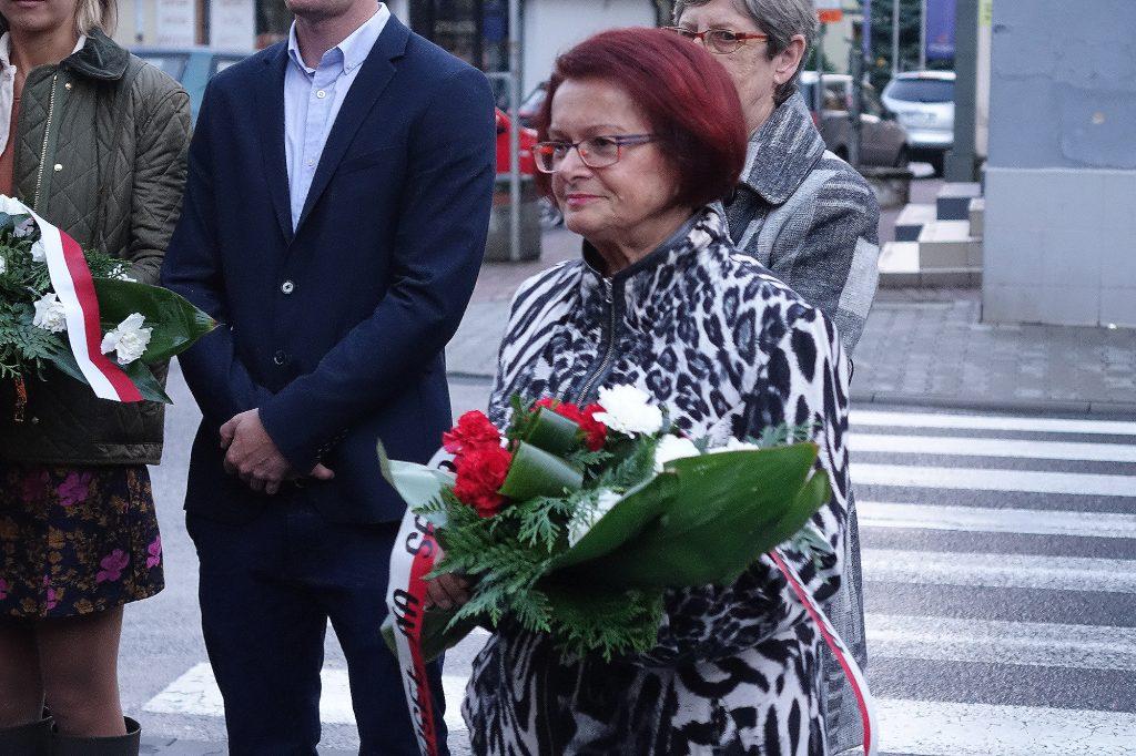 Maria Kurowska składa kwiaty pod tablicą bł. ks. Jerzego Popiełuszki w Jaśle